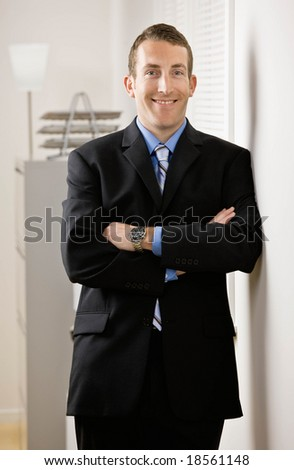 Confident businessman with arms crossed leaning on wall