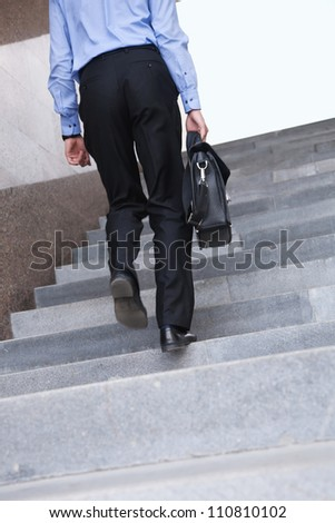 Confident businessman with suitcase walking the stairs