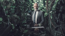 Confident businessman working in the jungle, he is connecting with his laptop and smiling