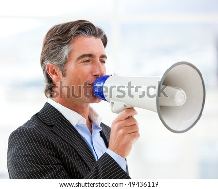 Confident businessman yelling through a megaphone in the office