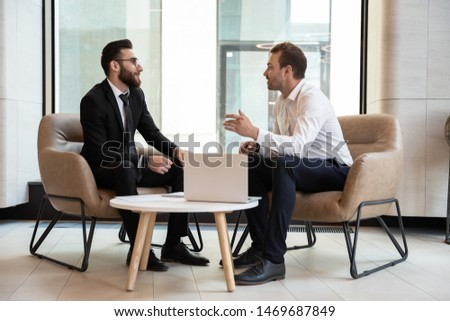 Confident businessmen discussing deal, sharing startup ideas at meeting, business partners negotiations in modern office with panoramic windows, colleagues talking, working on project together