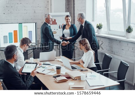 Confident businessmen shaking hands and smiling while working together with colleagues in the board room