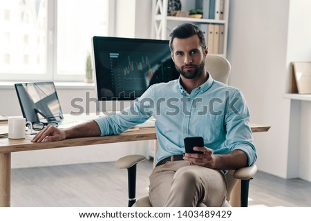 Confident businessmen. Young modern businessman looking at camera while sitting in the office