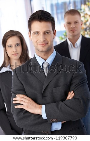 Confident businessteam, focus on smiling elegant businessman standing with arms crossed, looking at camera.