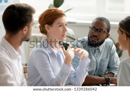 Confident businesswoman, coach discussing project with diverse colleagues at briefing in boardroom, sharing thoughts, ideas, employees attentively listen to team leader, staff training concept