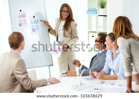 Confident businesswoman commenting marketing results to colleagues at meeting