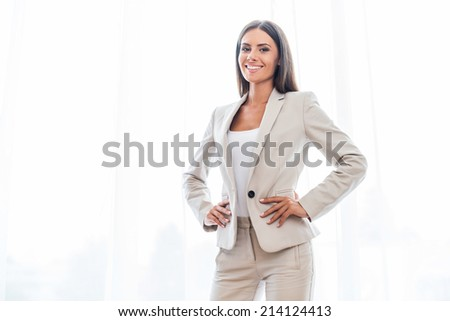 Confident businesswoman. Confident young businesswoman in suit holding hands on hip and smiling