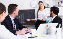 Confident businesswoman doing presentation to colleagues on blackboard with graphs and diagrams