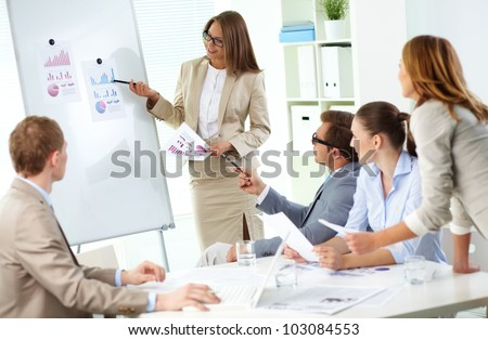 Confident businesswoman explaining her ideas to colleagues at meeting