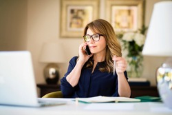 Confident businesswoman having a business call while working from home. Home office.