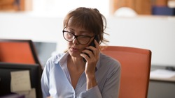 Confident businesswoman in glasses consulting client on cellphone in office, busy employee solving business problem online, having serious conversation, phone negotiations, horizontal photo