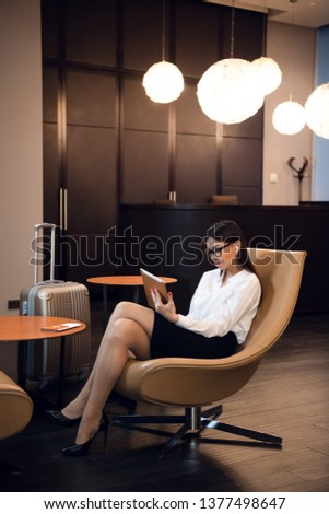 Confident businesswoman listening music on her tablet computer while sitting in chair in airport business lounge #1377498647