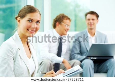 Confident businesswoman looking at camera at background of communicating men
