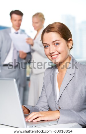 Confident businesswoman looking at camera while typing at background of communicating people