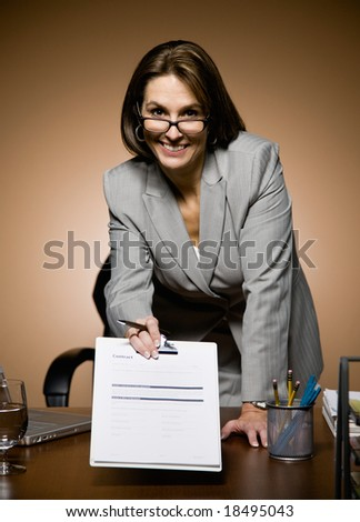 Confident businesswoman offering clipboard with contract for signature