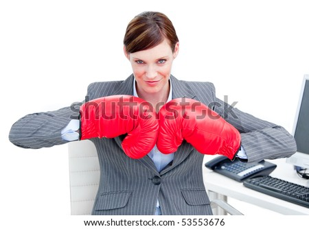 Confident businesswoman preparing to fight with boxing gloves in the office