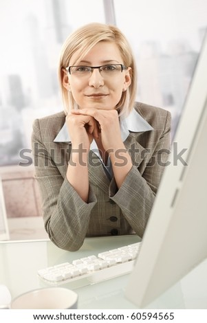 Confident businesswoman sitting at desk, smiling at camera.?