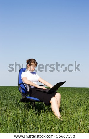 Confident businesswoman sitting in an armchair on the field - stock photo