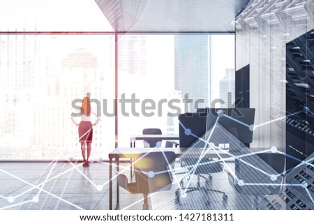 Confident businesswoman standing in panoramic office with wooden bookcases and computer tables. Double exposure of graphs. Concept of stock market. Toned image #1427181311