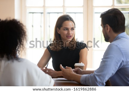 Confident businesswoman team leader holding briefing with diverse colleagues, discussing strategy, project plan, giving instructions to workers, business partners negotiation in boardroom