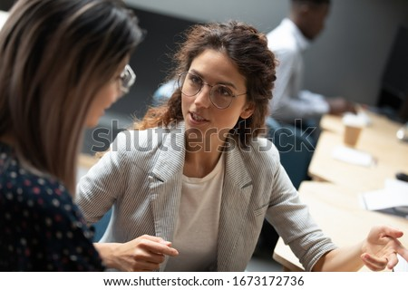 Confident businesswoman wearing glasses discussing project with colleague close up, diverse employees working together, executive consulting Asian woman client, mentor teaching trainee in office