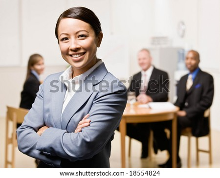 Confident businesswoman with co-workers in background