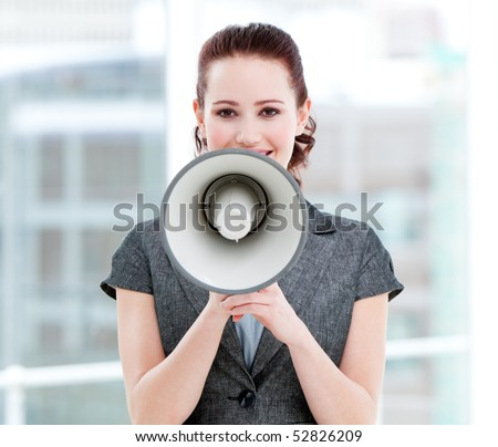 Confident businesswoman yelling through a megaphone standing in the office - stock photo