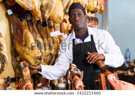 Confident butcher working behind counter in delicatessen store, checking quality of jamon
