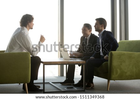 Confident candidate answering smiling hr managers questions in job interview, two recruiters in suits listening to applicant, making hiring decision, employee making offer to business partners