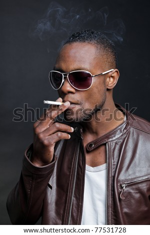 Confident Casual Young Black Man Wearing Brown Leather Jacket And Sunglasses Smoking Cigarette. Studio Portrait Against Dark Background