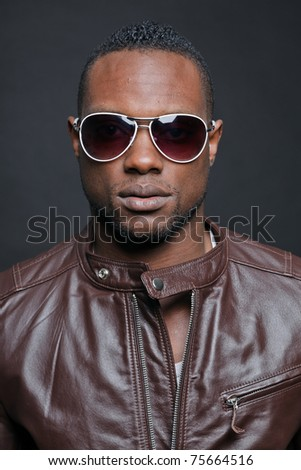 Confident casual young black man wearing brown leather jacket and sunglasses. Studio portrait against dark background.