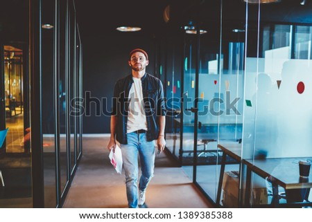 Confident casually dressed businessman walking in modern interior office thoughtfully ,serious caucasian guy having successful career in corporation, full length of male hipster in company