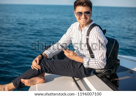 Confident caucasian business man with lether backpack handling an order over the phone and with his laptop while sailing on yacht trip at sea #1196007100