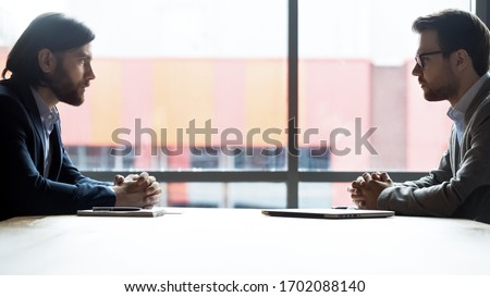 Confident Caucasian businessmen sit opposite at office desk debate in boardroom, serious male business opponents or competitors look at each other at briefing, rivalry, confrontation concept Foto stock ©