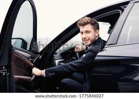Confident Chauffeur. Guy in suit sitting in driver's seat, getting in his car at downtown area, closing the door Foto stock ©
