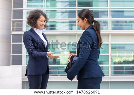 Confident colleagues standing on street and talking. Cheerful young confident employees wearing formal suits transferring documents. Business confidence concept #1478626091