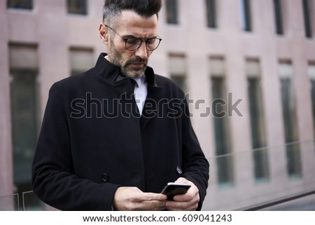 Confident concentrated businessman 40 years old typing text to colleague on mobile phone. Stylish handsome man with glasses sending someone important messages using SMS on smartphone on street #609041243