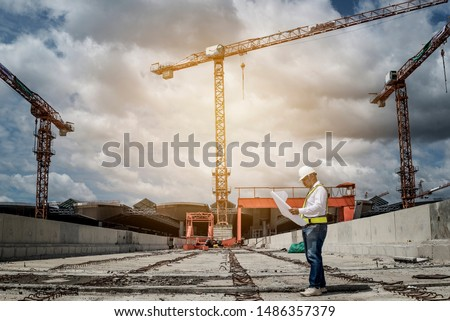 Confident construction engineer in hardhat  on  Site under development.Construction engineers supervising progress of construction project onsite construction with crane on background.