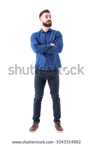Confident cool young bearded man standing and looking away with crossed hands. Full body isolated on white background.