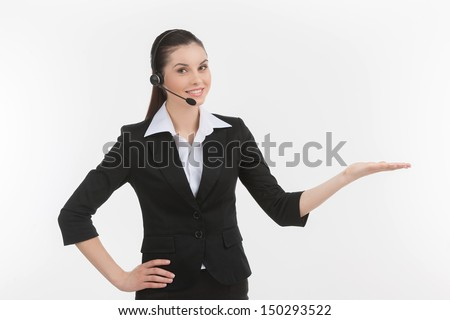 Confident customer service representative. Cheerful young female customer service representative in headset gesturing while isolated on white