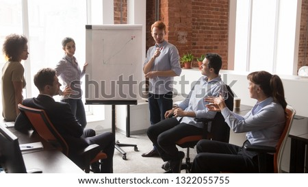 Confident diverse business managers coach speaker give corporate flip chart presentation consulting training employees group, mentor leader explaining discussing graph at office team meeting workshop