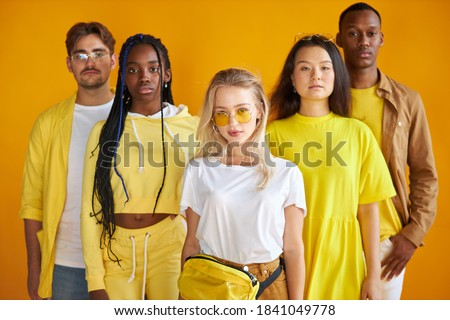 confident diverse mult-ethnic group of people stand together, isolated on yellow background, stylish african caucasian and asian youth Foto stock ©