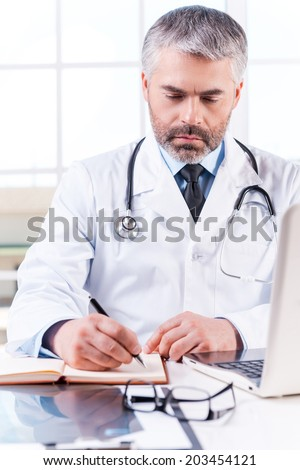 Confident doctor at work. Mature grey hair doctor writing something in note pad while sitting at his working place