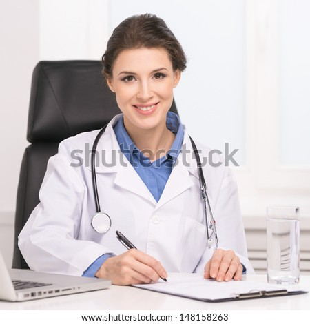 Confident doctor. Confident middle-aged female doctor sitting at her working place and writing something at the note pad