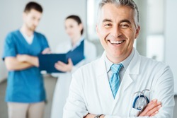 Confident doctor posing and smiling at camera and medical staff checking medical records on background