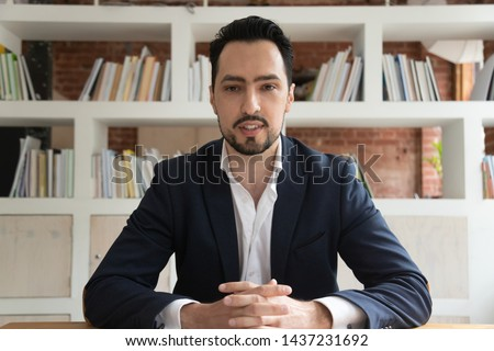 Confident eastern businessman entrepreneur in suit looking talking to camera, young ceo coach webinar speaker trainer recording vlog online business training make conference video call, webcam view