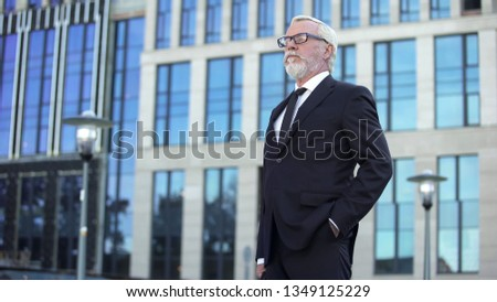Confident elderly businessman standing outside office building, male director