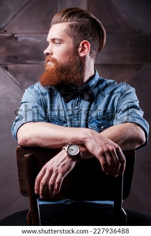 Confident elegance. Profile of a handsome young bearded man looking away and sitting on chair