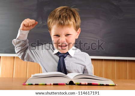 Confident elementary aged schoolboy sitting at the desk
