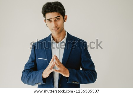 Confident enterprising male manager touching tips of fingers while contemplating about business. Serious successful young Indian businessman thinking of decision. Introspection concept